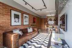 Olha que bacana a combinação de elementos que compõem esse projeto do nosso escritório! Os tons da parede de tijolinhos e do sofá se relacionam de forma harmoniosa, assim como o preto e branco do tapete geométrico que complementa os quadros assinados pelo arquiteto Leandro Neves. Foto: Alessandro Giraldi