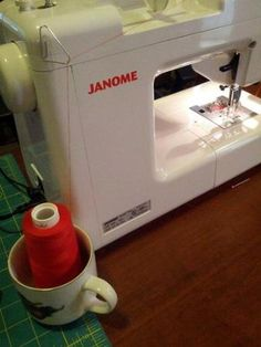 Genius! Paper clip taped to the back of the machine and a coffee mug to hold the thread cone.