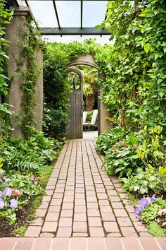 A brick path with a pergola beckons visitors to the pool.