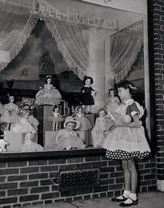 Vintage photo of a little girl in front of a New York Doll Hospital, 1954.
