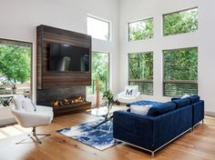 The fireplace backed by dark wood paneling provides a focal point in the living room, its heavier look balanced by the blue sofa opposite.