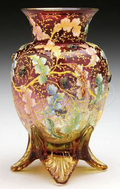 "MOSER DECORATED AND APPLIED VASE. Moser vase has cranberry shading to clear body with applied amber glass foot. Vase has allover decoration of colorful oak leaves in red, yellow, green and blue with yellow branches. Vase has a single enameled bumblebee at the shoulder and is further decorated with applied and gilded glass acorns. Signed on the underside in gold ""622/D180 Moser""."