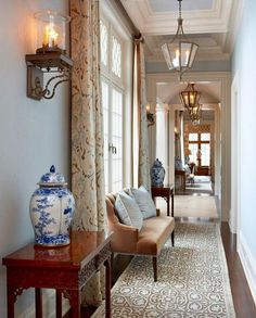 Traditionally decorated hallway: candle sconces, veneer bench, mahogany side tables, chinoiserie vases • via @ rinfretltd