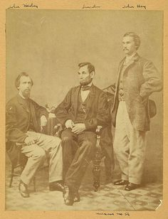 "President Abraham Lincoln seated between his private secretaries John G. Nicolay and John Hay at a photo session in Alexander Gardner's studio in Washington, D.C., on November 8, 1863.  ""On this day John Hay wrote in his diary: 'Went with Mrs. Ames to Gardner's Gallery & were soon joined by Nico (John G. Nicolay) and the Prest. We had a great many pictures taken ... some of the Prest. the best I have seen. ... Nico & I immortalized ourselves by having ourselves done in a group with the…"