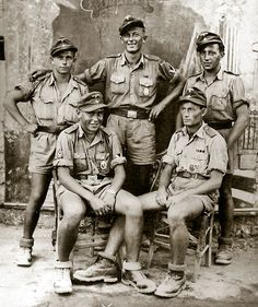 Afrika-Korps buddies pose for a group photograph at a civilian photographer's shop; undisclosed location, probably c. 1942. Note the alpine heavy boots they all wear, perhaps an indication of the unit they served in before being transferred to Africa.