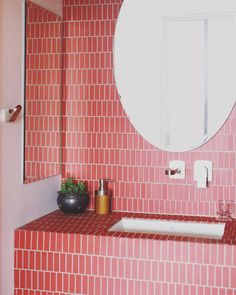 Bathroom with pink ceramic tile on bathroom wall and frameless round mirror. Bathroom Red, Bathroom Wall Tile, Bathroom Inspiration, Pink Bathroom, Tile Trends, Beautiful Bathrooms, Bathroom Furniture, Bathroom Interior Design, Bathroom Design