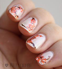White nail polish with orange Cherry Blossoms