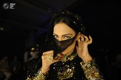 Model Tatmain, wearing creations by designer Nadya Mistry, fixes her dress before taking to the the catwalk during the final day of the Bridal Couture Week in Karachi. INSIYA SYED/REUTERS
