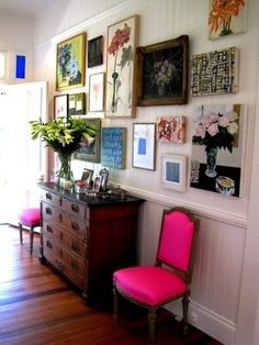 """Very cool mix of vintage floral paintings.  The colors and frames don't exactly """"match""""-- but the common theme unifies the gallery wall. Of course, I love the vintage dresser and chairs that have been boldly updated with neon fuscia fabric."""