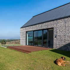 House featuring walls built from rock-filled cages.