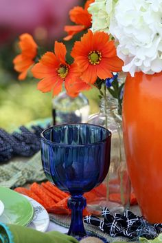 Summer tablescape -- love the orange vase with white flowers in the far right of the photo!  They echo the orange flowers in the clear glass bottle.
