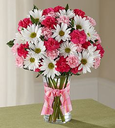 "Sending a Sweet Surprises® Bouquet by FTD® is an absolutely charming way to send your warmest sentiments. Hot pink mini carnations, pink mini carnations, white traditional daisies and lush greens are sweetly situated in a classic clear vase accented with a perfectly pink designer ribbon to create a bouquet that will delight your special recipient at every turn.GOOD bouquet is approximately 15""H x 12""W.Your purchase includes a FREE personalized gift message."