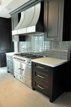 Gorgeous kitchen design with ebony kitchen cabinets, La Cornue Range, French curve range hood and blue glass tiles backsplash.