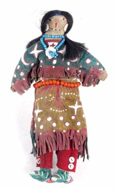 """Double Doll hand made by the Lakota Sioux Native Americans, (circa 1890-1910). The piece features a unique and rare design of being two unique dolls having different faces and outfits on both sides. The piece is constructed with a canvas body, Native Tanned Leather with numerous Ghost Dance figures, red Hudson Bay white heart Trade Beads, and human hair. The piece was collected from Chamberlain South Dakota. Measures 12"""" long. This is both trade cotton and sinew sewn."""
