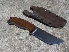 "RedEyedJack custom knives. REJck. This classic hunting/survival  knife is made from 3/16"" 1095 high carbon steel. 90% flat ground. Ipe wood handle scales with nickel silver pins. Brown kydex sheath. This knife is SOLD. Handmade in the U.S.A. with pride. Find us on Facebook REJck RedEyedJack custom knives of Bonifay, Florida E-mail redeyedjackcustomknives@yahoo.com"