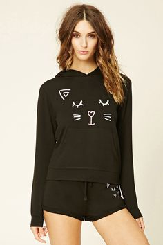 A lightweight knit hoodie featuring a sleeping cat face with a heart nose on the front, a kangaroo pocket, long sleeves, and protruding ears on the hood. Matching shorts available.