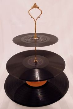 Vinyl-Record Cake stand. ~ Three-tiered cake stand made of vinyl records, separated and held together by metal spindles with an ornate handle at the top.