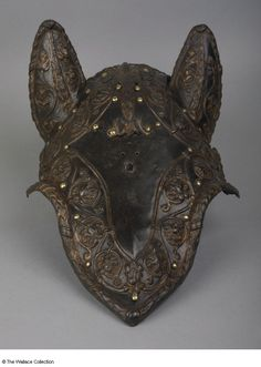 Demi-shaffron  Possibly  Caremolo Modrone (1489 - 1543)		  Italy, possibly Mantua or Milan  c. 1540   Banded low- to medium-carbon steel, extensively hot-worked, and gold, embossed, russeted and gilded