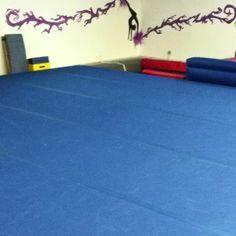 Gymnastics floor in the basement-- and uneven bars, a balance beam, wedge mat, and an inground trampoline. #dreambasement #gymnastics #futurekids