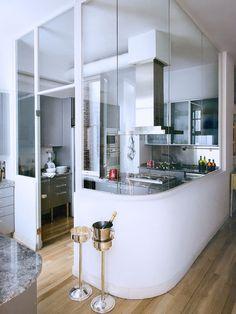Une cuisine avec des vitres transparentes pour voir ce qui se passe dans la salle à manger mais pour que les odeurs restent en cuisine et pourquoi une vitre coulissante pour faire bar quand on est peu à manger
