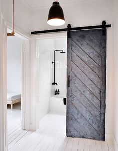 I the rustic, white-painted wooden floor that covers all the rooms, even the bathroom. The old barn door that leads into the bathroom is so pretty and adds some roughness to this clean, white house Bathroom. WABI SABI Scandinavia - Design, Art and DIY. The Doors, Sliding Doors, Front Doors, Entry Doors, Sliding Cupboard, Hall Cupboard, Old Barn Doors, Wooden Doors, Timber Door