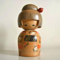 Il s'agit d'une poupée kokeshi japonaise sosaku vintage. Faite de bois. Il est sculptés et peint à la main avec des motifs floraux (kimono fleuri). Il est signé par l'artiste Miyashita Hajime. Japon. Il y a des signes d'usure en raison de l'âge. La peinture est un peu abimée. Mais,
