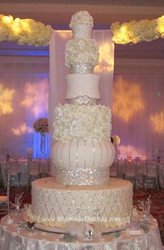 "This towering cake is over 7' tall with a 46"" wide base. Accented with yards of bling & hundreds of sugar flowers, this is sure to be a focal point at any reception. By www.WhoMadeTheCake.com"