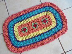 Tapete oval confeccionado com barbante de excelente qualidade.  Em destaque : centro com 3 flores vermelhas.  Cor disponível : Da foto. R$ 48,00