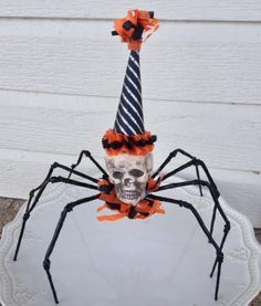 Halloween decoration Halloween ornament A large bendable spider has sprouted a skeleton head EEK!.. The head is wearing a fancy party hat with a crepe paper ruffle. He has a collar made from tissue trim.