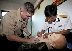 DA NANG, Vietnam (April 24, 2012) Hospital Corpsman 2nd Class Adam Martin, left, with the III Marine Expeditionary Force Tactical Medical Simulations Center, observes a medical officer from the Vietnamese People's Navy insert a needle into a mannequin during a basic lifesaving course, part of Naval Exchange Activity Vietnam. (U.S. Marine Corps photo by Cpl. Patricia D. Lockhart)