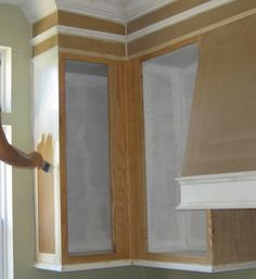 How to paint cabinets, make a range hood, close the space above the cabinets, add crown molding, marble back splash.  Love it.
