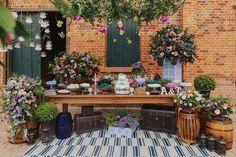 Mesa de doces com estilo rústico, em madeira com arranjos em tons de rosa e lilás. Produção da madame Fiori na Fazenda Vassoural. Foto: Frankie e Marília