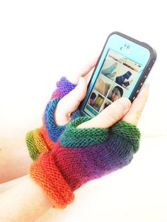 These wonderfully warm green, red, orange, and blue hand knitted fingerless mittens are the perfect weight for the spring. A light merino wool yarn will