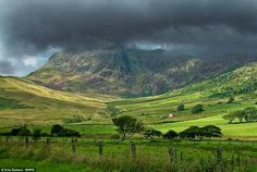 Dark skies: Rain clouds gather over the Mynydd Moel mountain in the Cader Idris range in north Wales. The top of the mountain is completely covered   Read more: http://www.dailymail.co.uk/sciencetech/article-1363789/The-cloud-chaser-Amateur-weatherman-follows-sun-compass-snap-stunning-pictures.html#ixzz1FwwYBwa3