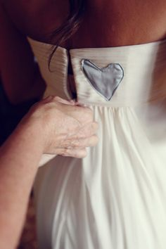 In loving memory of her father, she had his favorite baby blue silk scarf embroidered as a heart onto the back of her wedding dress