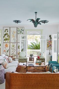 Sitting area with wicker furniture in living room design ideas. Eclectic, vintage inspired sitting area with palm leaf light fitting, french windows and framed floral prints.