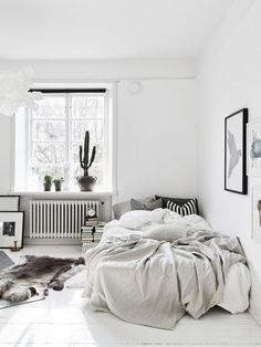 Swedish bedroom with a low lying bed and messy sheets