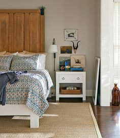 A reclaimed barn door serves as this master bedroom's headboard. The women nabbed the sisal rug at a Pottery Barn outlet. The walls are painted Smokey Taupe by Benjamin Moore.