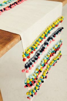 DIY Inspiration: Nomades Table Linen - anthropologie.com. Just sew rows of pom poms onto a table runner.