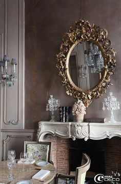 Great fireplace mantle with small crystal candelabras, and ornate mirror.