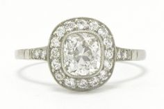 The Ojai Art Deco engagement ring. The shimmer of this over 1 carat old mine cushion diamond engagement ring is absolutely mesmerizing. Graded near colorless and blessed with fantastic clarity, the chunky facets of this beauty are brought to life in an Art Deco style halo, the bezel setting kissed with milgrain. Also known as a target ring, this iconic classic is a staff favorite. #diamond #engagementring #platinum #artdeco #artdecostyle #artdecoring #artdecorings #engagementrings #love #ido Estate Engagement Ring, Antique Engagement Rings, Diamond Engagement Rings, Cushion Diamond, Halo Diamond, Art Deco Ring, 1 Carat, Art Deco Fashion, Jewelry Stores