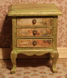 Miniature Dreams  There are many layers of paint in this chest of drawers: a pink base, then a lime green coat, then again brown patina and gold.  This is so beautiful!