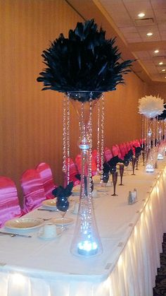Black feather ball with double flared vase and dangling crystals for a wedding head table. Wedding reception decorations provided by Kims Bridal, 20s Wedding, Head Table Wedding, Wedding Reception Decorations, Wedding Stuff, Mardi Gras Decorations, Star Decorations, Feather Centerpieces, Centerpiece Ideas, Pearl Themed Party