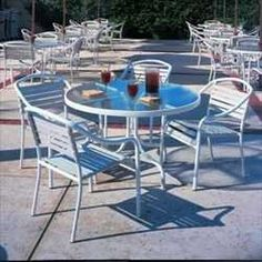 "Tamiami Dining Groups - 48"" Round Dining Table with 4 Dining Chairs - Aluminum Patio Furniture by Woodard. $899.00. Visit our site for Strap Color and Aluminum Finish options. Aluminum Patio Dining Groups - 48"" Round Dining Table with 4 Dining Chairs. Easy to care for with a symmetrical contemporary look, Tamiami is a terrific solution for a home pool area or a common area in a multi family dwelling.  Durable construction consists of a long lasting virgin vinyl ..."