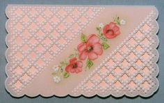 Pale and pretty pink card with overlay of grid work and cut out lace.