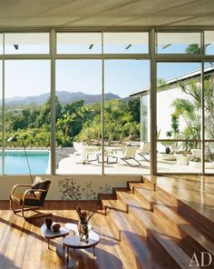 Window walls in the living area make the most of exterior sightlines, including the lush foliage and distant mountains beyond the pool and terrace. The Boyds replaced linoleum flooring with palm planks and arranged an Alvar Aalto armchair and Frederick Kiesler tables by the stairs.