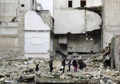 Children walk on the debris of a damaged building at al-Myassar neighborhood of Aleppo, Syria February 16, 2015. REUTERS/Hosam Katan