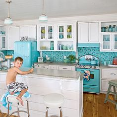 Retro Beach Kitchen: The punchy turquoise hue of the vintage-style appliance puts a chic spin on the space. A tumbled-glass backsplash mimics natural sea glass and contrasts the sleek concrete countertops. Reproduction pendant lighting and period barstools top off the soda fountain look the homeowners hoped to achieve.