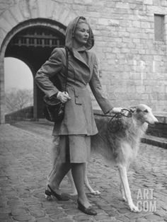 Model Wearing Hooded Suede Suit While Walking Her Dog on Cobblestoned Street Near Cloisters Museum Premium Photographic Print by Nina Leen at Art.com