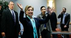 Then Democratic presidential hopeful Hillary Rodham Clinton waves to the overflow crowd as she walks with campaign aide Huma Abedin, right, and a secret service agent at a campaign event in Huron, S.D. | AP Photo